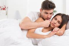 不快乐的年轻夫妇在卧室 库存照片