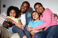 家庭坐一起看电视的沙发 免版税图库摄影
