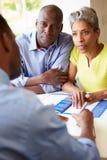 与财政顾问的成熟黑夫妇会谈 库存照片