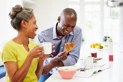 食用早餐和读杂志的夫妇在厨房 免版税库存照片
