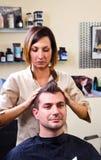 愉快的女性发式专家设置客户的头发 免版税库存照片