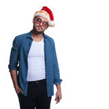 戴圣诞老人帽子的轻松的年轻偶然人 免版税库存照片