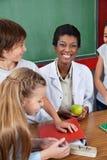 拿着与学生的老师苹果计算机站立在 图库摄影