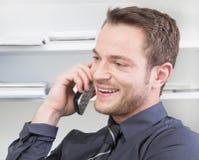 挥动在电话的愉快的人 库存图片