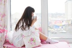 喝她的早晨咖啡的可爱的少妇 库存图片