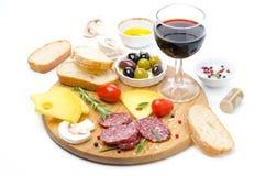 蒜味咸腊肠、乳酪、面包、橄榄、蕃茄和杯红葡萄酒 库存照片
