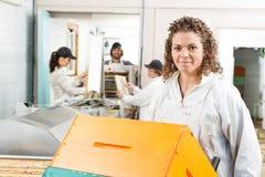 有被堆积的蜂窝条板箱的女性蜂农 免版税库存图片