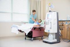 护士接受血液透析的覆盖物患者 库存照片