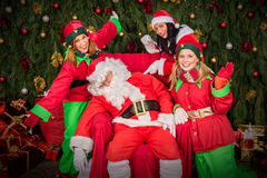 Утомленный Санта Клаус с стулом сна хелпера эльфа Стоковые Изображения