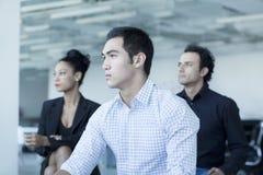 坐在业务会议的三个严肃的商人 免版税库存图片
