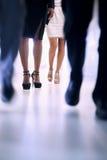 步行沿着向下在办公楼的走廊的低观点的人,在高跟鞋的焦点 库存照片