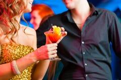 在酒吧或俱乐部饮用的鸡尾酒的年轻夫妇 图库摄影