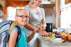 家庭-做学校的母亲早餐 免版税库存照片