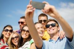 拍与智能手机的小组朋友照片 免版税图库摄影