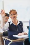 举她的手的快乐的女性成熟学生 图库摄影