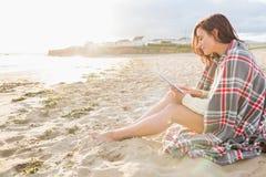 用毯子盖的妇女使用片剂个人计算机在海滩 免版税库存照片
