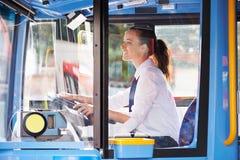 母公共汽车司机画象在轮子后的 库存图片