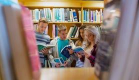 Σπουδαστές που διαβάζουν το βιβλίο στη βιβλιοθήκη κολλεγίων Στοκ Φωτογραφία