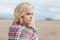 用毯子盖的妇女的侧视图在海滩 库存图片