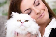 拿着一只波斯猫的美丽的少妇 免版税库存图片