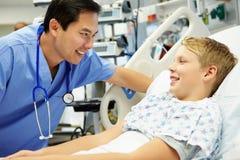 男孩谈话与男性护士在急诊室 库存图片