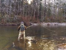 人在冷的冬天天气的用假蝇钓鱼 免版税库存照片