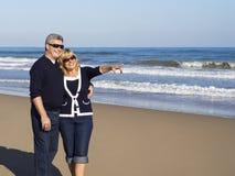 愉快的成熟夫妇指向一个晴天海滩 免版税库存图片