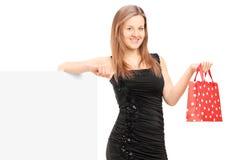 有站立在一个备用面板旁边的礼物袋子的年轻女性 免版税库存图片