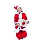 拿着礼物盒和跳跃充满喜悦的圣诞老人男孩 库存图片