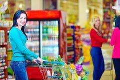 Χαμογελώντας γυναίκα που ψωνίζει στην υπεραγορά με το καροτσάκι Στοκ εικόνες με δικαίωμα ελεύθερης χρήσης