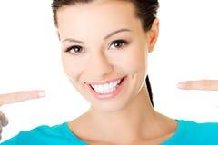 显示她完善的白色牙的美丽的偶然妇女。 免版税图库摄影