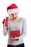 圣诞老人帽子和打开的礼物的美丽的妇女。 库存图片