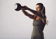 有吸引力的女性做的水壶响铃锻炼 库存照片