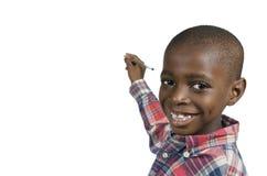 Αφρικανικό αγόρι που γράφει με το μολύβι, ελεύθερο διάστημα αντιγράφων Στοκ Φωτογραφία