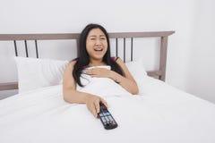 愉快的妇女在床上的看电视 免版税图库摄影