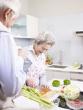 资深夫妇在厨房里 免版税库存图片