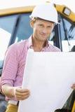 拿着图纸的男性建筑师画象在建造场所 免版税图库摄影