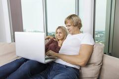 使用膝上型计算机的年轻夫妇在客厅在家 免版税库存照片