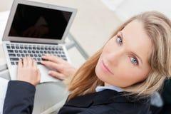 使用她的膝上型计算机的年轻专业女商人 图库摄影