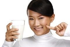 年轻愉快的亚洲妇女饮料新鲜的牛奶 免版税库存图片
