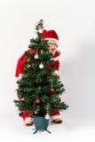 作为圣诞老人打扮的男婴掩藏在圣诞树后 免版税库存照片