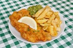 鱼和油炸物用豌豆在吃饭的客人。 免版税库存照片