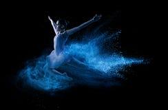 跳进蓝色粉末云彩的年轻美丽的舞蹈家 库存照片