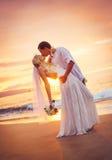 新娘和新郎,亲吻在一个美丽的热带海滩的日落 免版税图库摄影