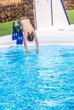 跳在蓝色水池的男孩 免版税库存图片