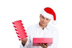 红色圣诞老人帽子开头礼物的年轻人和非常生气 免版税库存照片