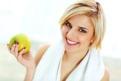 拿着绿色苹果的愉快的微笑的适合的妇女 免版税库存图片