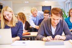 老师帮助的学生在学校 免版税库存照片