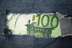 一百欧元票据通过被撕毁的蓝色牛仔裤纹理 免版税图库摄影