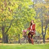 一辆自行车的美丽的女性在看照相机的公园 免版税库存照片